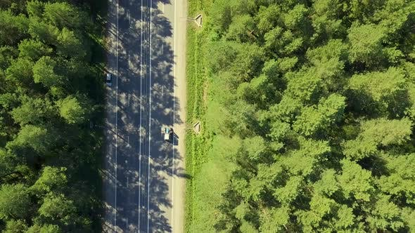 Thumbnail for Aerial: Flying Over Highway in the Forest. View Vertically Down on Passing Cars, Trucks