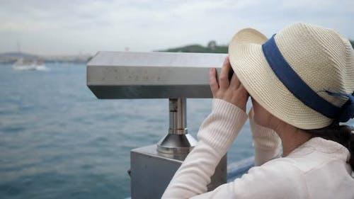 Woman Looks Through Binoculars Exploring Coast on Embankment