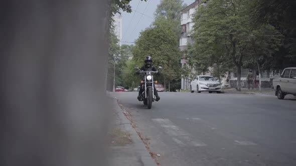 Thumbnail for Man or Woman Wearing a Motorcycle Outfit Riding a Biker Motorcycle Along a City Road