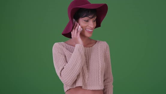 Thumbnail for Happy smiling black woman in floppy hat talking on smart phone on green screen