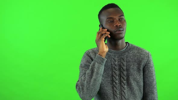 Thumbnail for A Young Black Man Talks on a Smartphone - Green Screen Studio