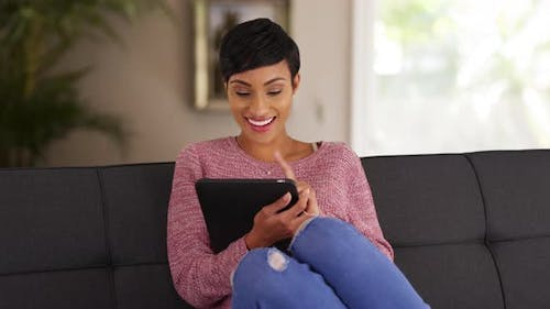 Portrait of black female in her 20s lounging on sofa using tablet in living room