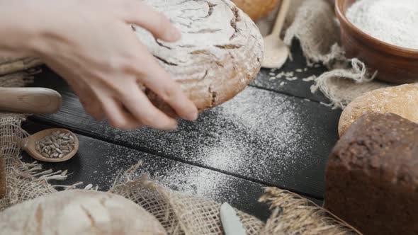Thumbnail for Brothintergrund - Verschiedene Brotsorten werden auf dem Tisch serviert, eine Frau legt einen fertigen Laib von