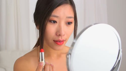 Chinese woman putting on makeup