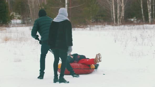 A Man Rolls His Child on the Inflatable Sled