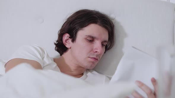 Closeup Portrait of Tired Young Man Falling Asleep As Reading in the Evening