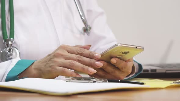 Thumbnail for Female Doctor Using Smart Phone Writing Notes