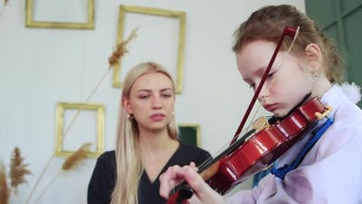Violin Lesson a Little Girl Playing Violin with a Bow in the Class and Her Teacher Sitting Next to