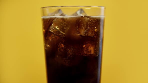 Thumbnail for Glass Full of Cola Fizzy Drink with Ice Cubes. Cold Sparkling Soda on Yellow Background