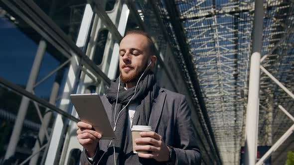 Thumbnail for Caucasian businessman using business app on tablet computer, walking in city