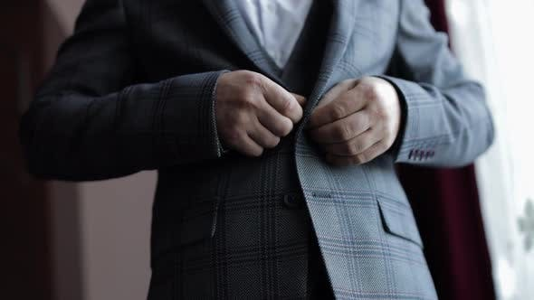 Buttoning Jacket Hands Close Up. Man in Suit Fastens Buttons on His Jacket Preparing To Go Out