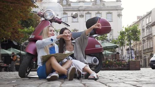 Likable Cheerful Female Friends Sitting on the Asphalt Near Scoote