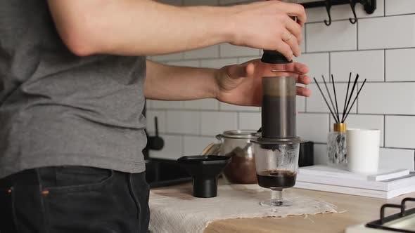 Barista macht Aeropress Schritt für Schritt. Kaffee auspressen.