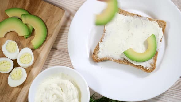 Thumbnail for The Girl Is Preparing a Healthy Breakfast - Toasts with Avocado and Tender Curd Cheese, Quail Eggs