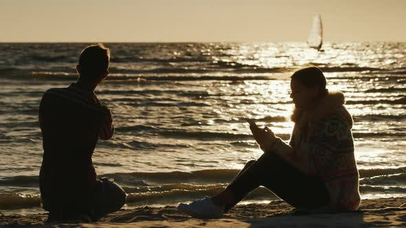 Thumbnail for Romantic Couple Relaxing on the Beach at Sunset. Woman Enjoying a Telephone, a Man Throws Stones