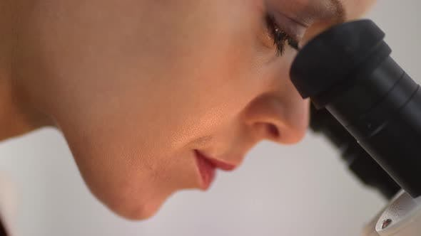 Thumbnail for Close up side view of medical researcher looking into microscope
