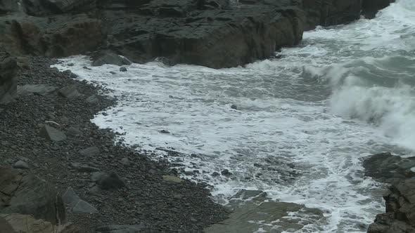 Waves breaking into foam on a rocky beach in Maine.