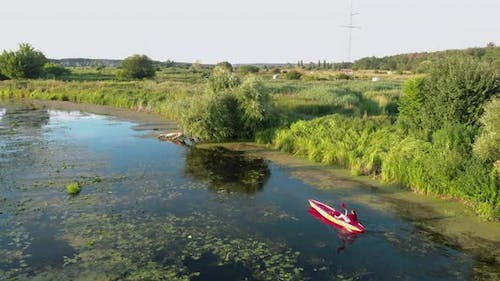 Woman is kayaking on river at countryside at sunset. Tourist is floating in canoe in summer.
