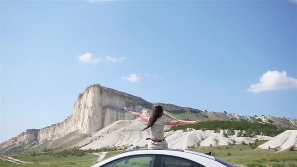 Thumbnail for Happy Girl Sitting on Roof of Her Car, Relaxing and Enjoying Road Trip