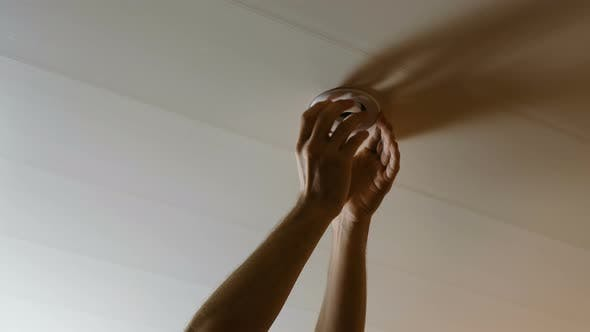 Thumbnail for Men's Hands Twist the Light Bulb in the Ceiling Electric Energy-saving Lamp