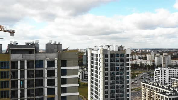 Thumbnail for Drone Flying Along High Rise City Tower Apartment Blocks Under Construction Towards National Library