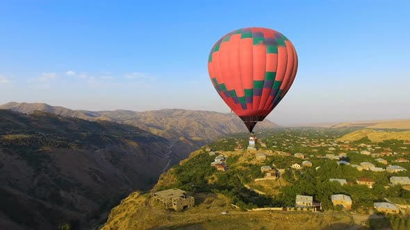 Thumbnail for Aerial View of Beautiful Hot Air Balloon Flying Over Mountain Village, Armenia