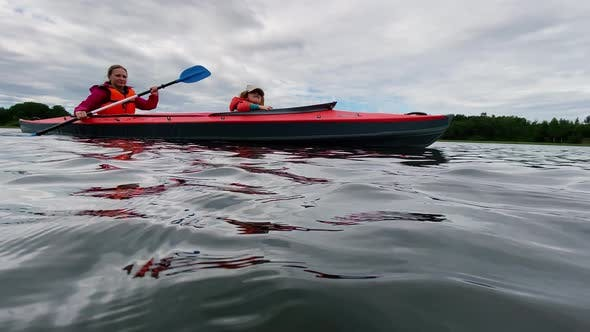 Cover Image for Woman Rows Sports Kayak with Daughter Along Lake Water