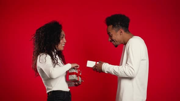 Thumbnail for Young African American Couple Exchange Gifts on Red Studio Background.