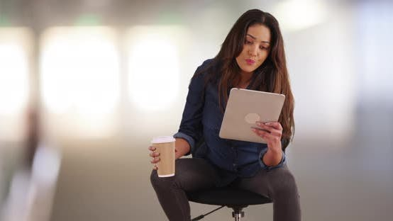Thumbnail for Successful Mexican female drinking coffee, using tablet in office building