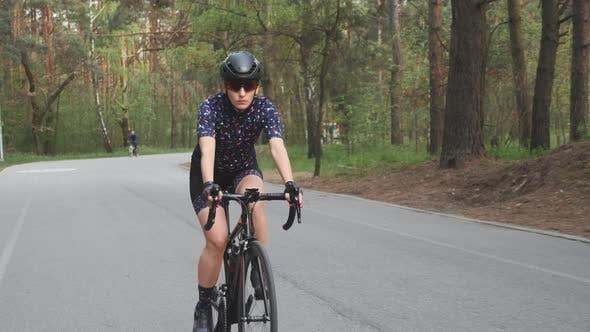 Thumbnail for Fokussierte professionelle Radfahrerin Reiten Rennrad in City Park Training für Rennen