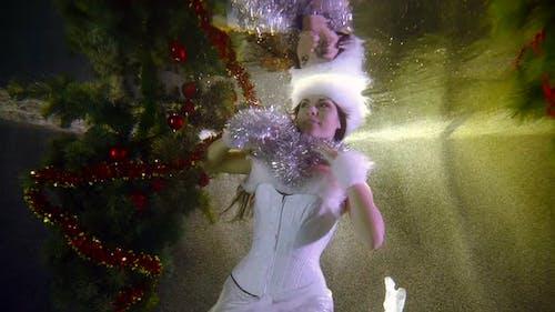 Winter Zauberin Frau spielt Silber-Lametta Unterwasser im Pool mit Weihnachtsbaum