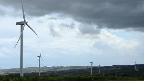 Thumbnail for Time-Lapse of Wind Turbine Propellers Rotating in Green Field, Dark Cloudy Sky