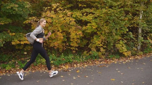 Happy Woman Enjoys Running in the Fresh Air, Sunny Warm Autumn Day
