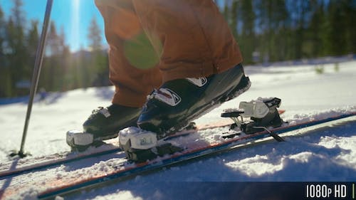 Downhill Skier Clipping Ski Boots into Ski Bindings in Slow Motion