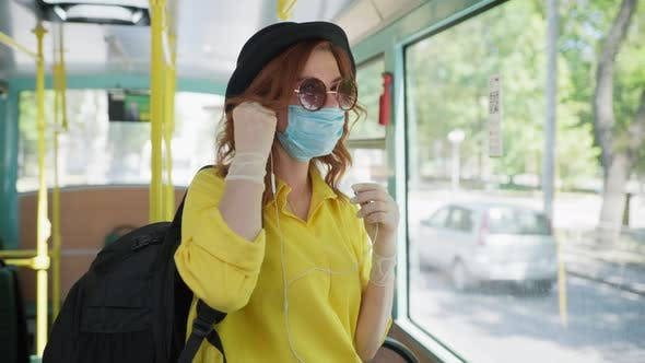 Coronavirus Travel, Attractive Girl with Glasses in Hat and Earphones Observes Safety Precautions