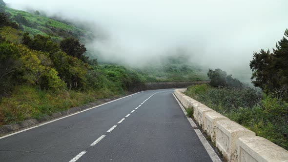 Thumbnail for First-person View of Motion Along a Mountain Road at Cloud Level, Slopes Covered with Green