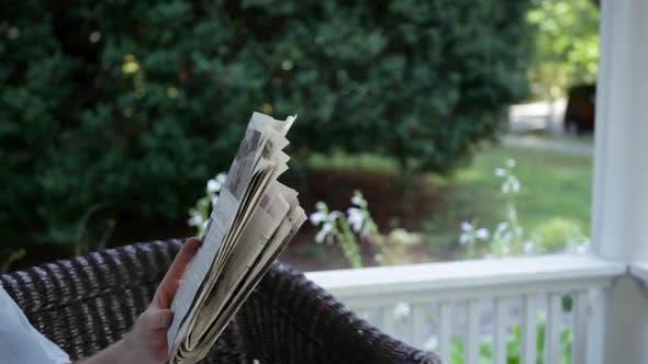 Thumbnail for Senior man reading newspaper and drinking lemonade