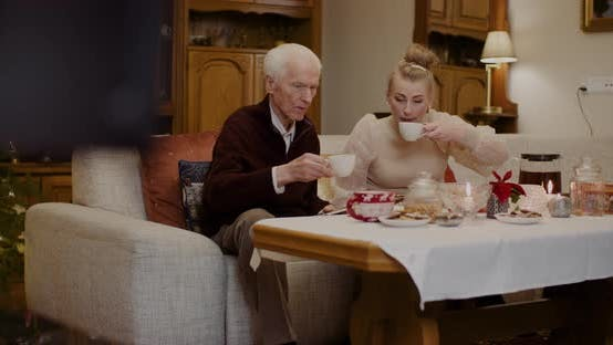 Woman Pouring Black Coffee In Cup For Grandfather During Christmas