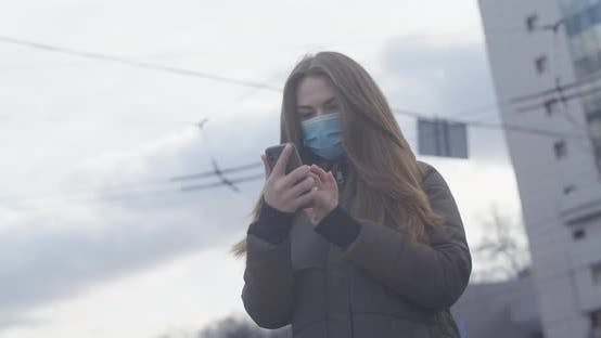 Thumbnail for Middle Shot of Young Woman in Protective Mask Using Smartphone As Standing in City at the Background