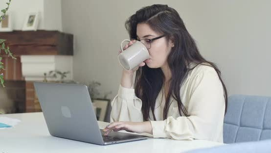 Thumbnail for Young Intelligent Caucasian Woman in Eyeglasses Drinking Tea or Coffee and Typing on Laptop