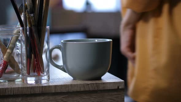 Cover Image for Coffee Cup and Artistic Equipment on Work Table