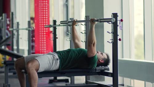 Young Man Flexing Muscles, Exercising on Barbell Bench with Crossbar in Gym Interior