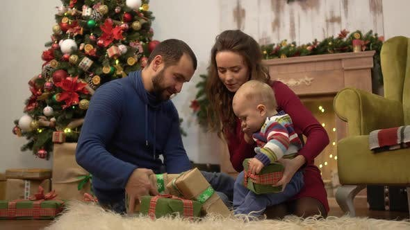 Cover Image for Mother, Father and Little Baby Sitting on the Floor in the Room with Christmas Decoration