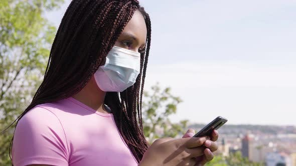 Thumbnail for A Young Black Woman in a Face Mask Works on a Smartphone, Closeup, Trees and a Cityscape