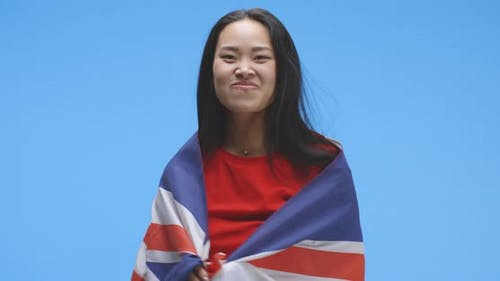Young Woman Wrapped in and Dancing with Union Jack