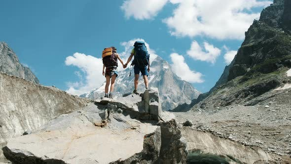 Thumbnail for Couple of Tourists with Backpacks in the Campaign Raise Their Hands Up on the Top of the Mountains