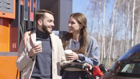 Thumbnail for Loving Couple Filling Up Car and Drinking Coffee