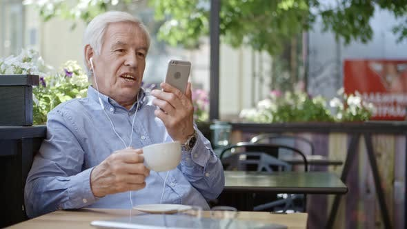 Thumbnail for Senior Man Video Conferencing on Smartphone in Cafe