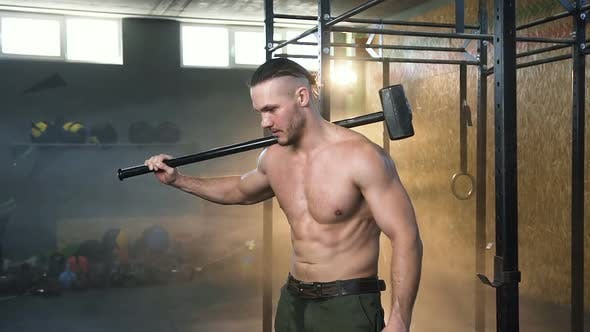 Thumbnail for Dolly Shot of Caucasian Strong Man with Hammer in the Gym