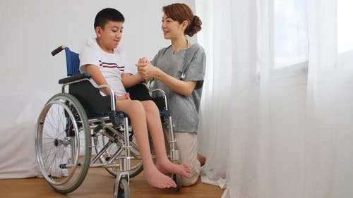 A physical therapist is talking to a disabled boy in a wheelchair.